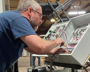 employee working with paint booth control panel